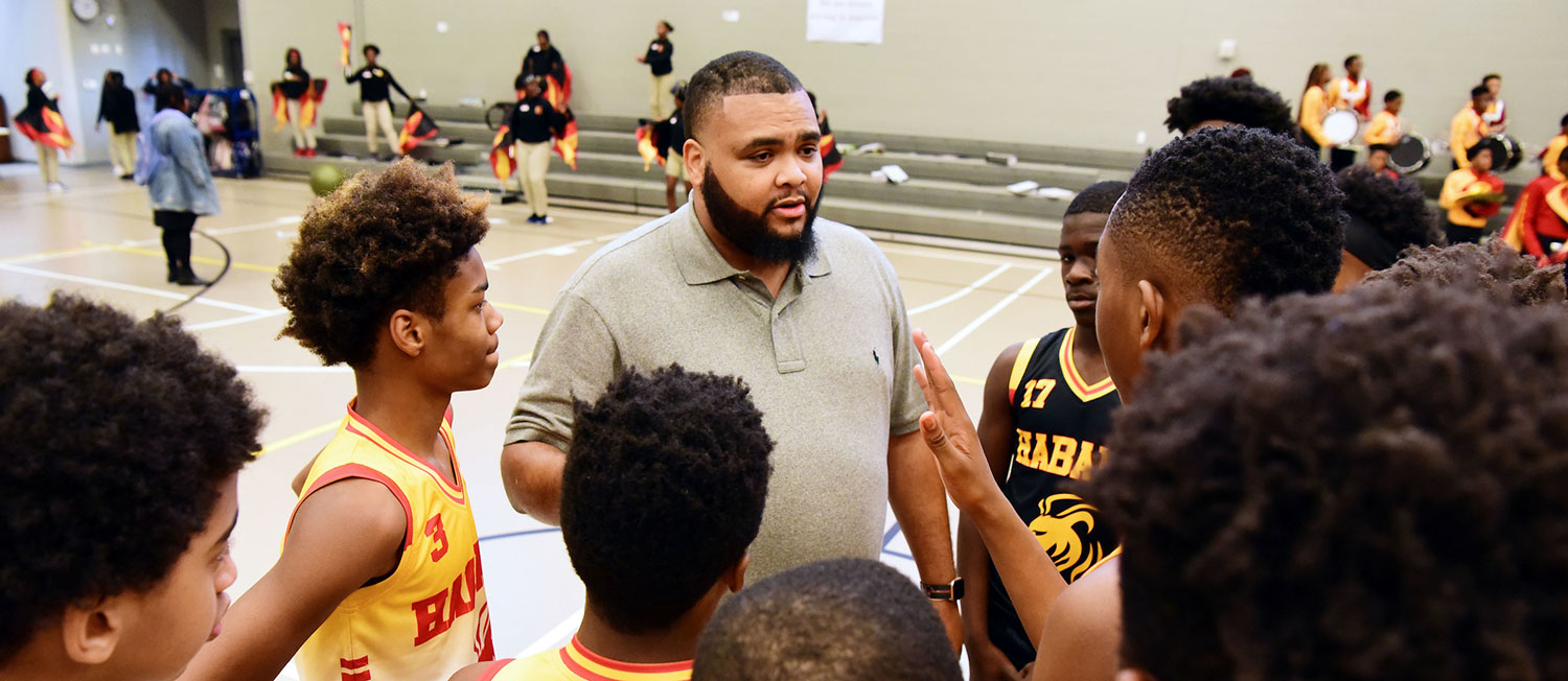 Gym coach helping student basketball players